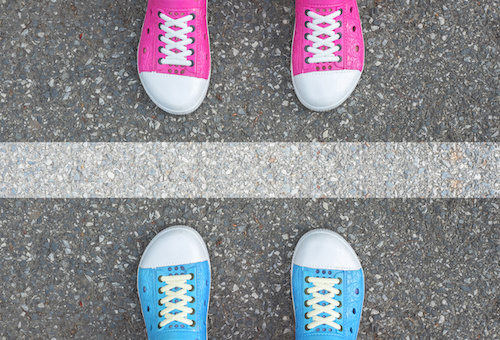 Blue shoes and pink shoes standing on asphalt concrete floor and white line between them