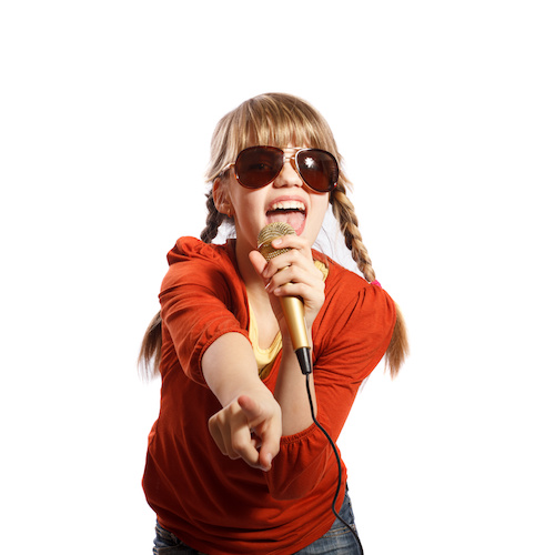 Girl singing into a microphone on a white background