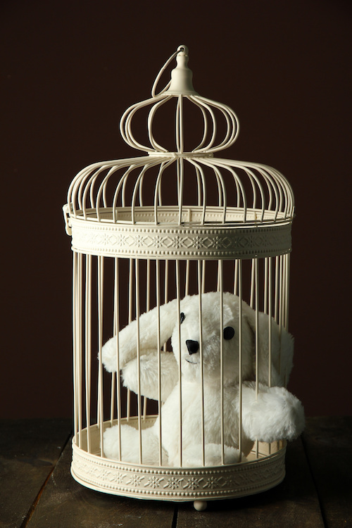 Toy rabbit in decorative cage on wooden table, on brown background
