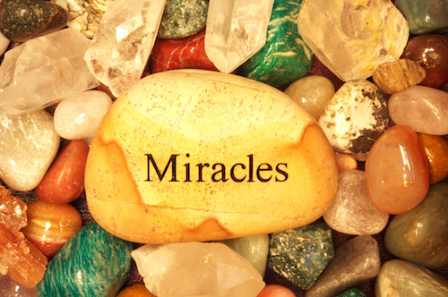 Stones and Crystals with a rock the says miracles on it